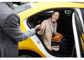 绅士帮助年轻女子离开出租车_5402024