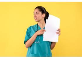 拿着纸的正面图祝福相当女性医生站立在黄色_13805354