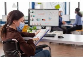有保护面具的残疾女商人工作在新的正常的商_15854122