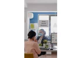 有医疗面罩的女商人谈话在有伙伴的智能手机_15876800