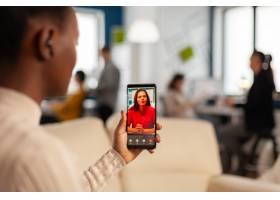 在使用手机的黑人员工肩膀与伴侣在启动营业_16097248