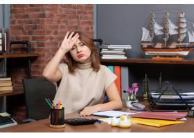 坐在书桌的疲倦的女商人正面图在办公室_16285640