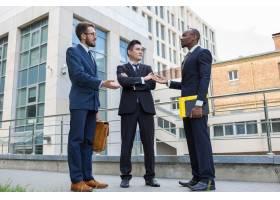 多族裔企业队画象站立反对城市的背景的三个_10129015