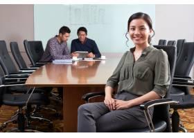 女性商业主管坐在与她的同事的办公桌工作在_5699157
