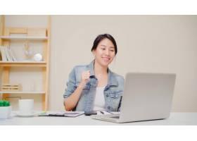 工作在书桌上的年轻亚裔妇女使用膝上型计算_4396316