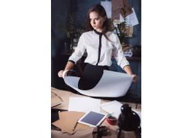 工作在绘图桌上的建筑师妇女在办公室或家_16077802