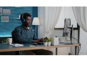 使用耳机的年轻人听音乐当在计算机上工作_15854082