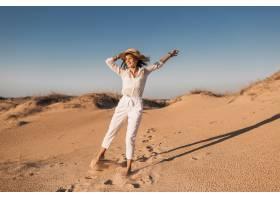 跑和跳跃在白色成套装备的沙漠沙子的时髦的_14105583