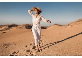 跑和跳跃在白色成套装备的沙漠沙子的时髦的_14105588