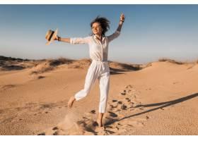 跑在沙漠沙子的时髦美丽的微笑的快乐的妇女_14105594