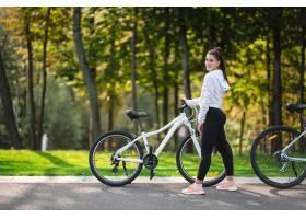 摆在白色自行车的美丽的少妇_13652737