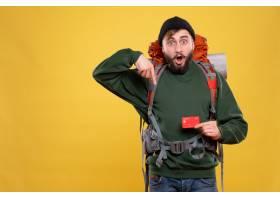 旅行概念與驚奇的年輕人有背包和拿著向下指_13578872