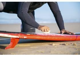 在潛水服打蠟沖浪板的男性沖浪板在沙子在海_13996215
