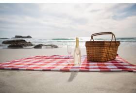 兩杯香檳瓶和野餐籃子在海灘毯子上_991225