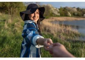 一顶帽子的可爱的女孩在日落的在湖的步行_15836308