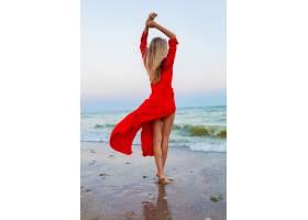 紅色禮服的美麗的自由婦女在風的風在海灘走_13977788