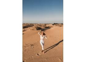 走在沙漠沙子的时髦的美丽的妇女在白色长裤_14105413