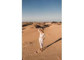 走在白色成套装备的沙漠沙子的时髦的美丽的_14105425