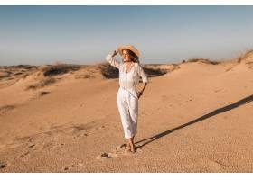 走在白色成套装备的沙漠沙子的时髦的美丽的_14105564