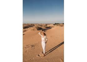 走在白色成套装备的沙漠沙子的时髦的美丽的_14105571