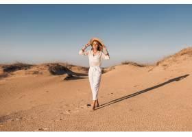走在白色成套装备的沙漠沙子的时髦的美丽的_14105577