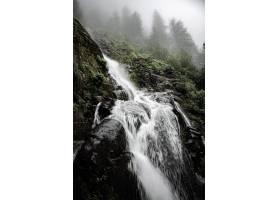 巖石峭壁和樹圍攏的一個強大的瀑布的美好的_14192237