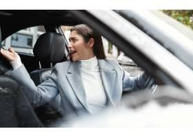 驾驶汽车的女实业家看起来懊恼后面和抱怨_13869236