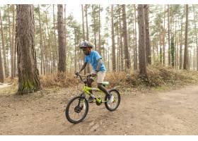 骑自行车的男孩在森林_13761847