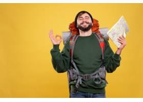 与微笑的年轻人的旅行概念有背包和拿着地图_13578855