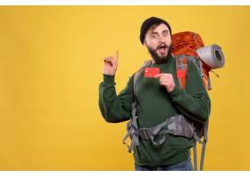 与惊奇的年轻人的旅行概念有背包和拿着在黄_13578874