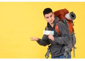 与拿着在黄色的红色背包的前视图酷旅客人_13579813