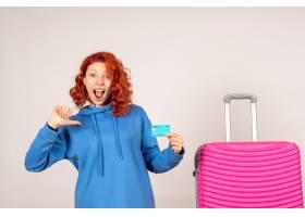 与桃红色袋子和拿着银行卡片的正面图女性游_13903925
