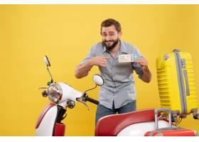 与站立在有手提箱的摩托车后的微笑的年轻人_13578866