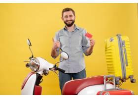 与站立在有手提箱的摩托车后的微笑的年轻人_13578868