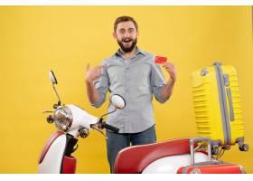 与站立在有手提箱的摩托车后的微笑的年轻人_13578870