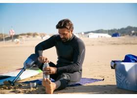 严肃的残疾人坐海滩和打开热水瓶_13996289