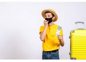 与站立近的黄色手提箱的草帽的迷茫的年轻人_13579796