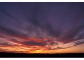 紫色和橙色天空的美好的射擊與云彩的在日落_7810416