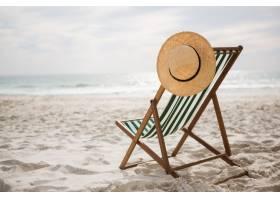 草帽在空的海灘椅子存放_991201