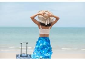 有站立與在美妙的海背景的手提箱的帽子的美_16303612