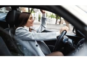 商业驾驶汽车和挥动手的愉快的女商人在朋_13869216