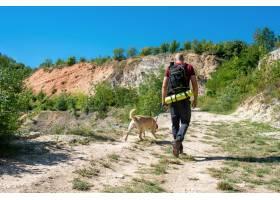 探索与他的狗的年轻白种人男性旅游美丽的地_15915738