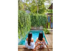 放松由一個游泳池的年輕有吸引力的夫婦在一_15877201