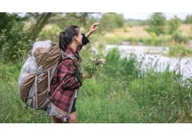 有一个大旅行背包和野花花束的可爱的女孩_16202318