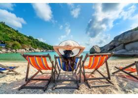 有帽子的妇女坐在椅子海滩在美丽的热带海滩_13250004