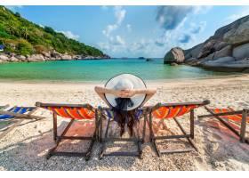 有帽子的妇女坐在椅子海滩在美丽的热带海滩_13250006