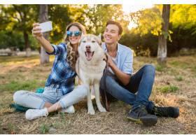凉快的年轻时髦的夫妇使用与狗在公园_13977534