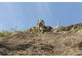 爬上山的一個年輕遠足者的低角度射擊_15915482