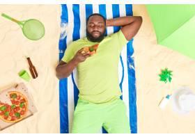 男子在海滩上吃披萨在暑假期间穿着绿色T恤_16074765