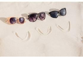 笑脸和三个太阳镜在沙子上_991299